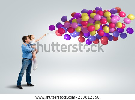 Happy father and daughter with bunch of colorful balloons - stock photo