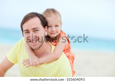 Happy father and his adorable little daughter at beach