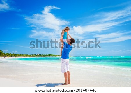 Happy father and his adorable little daughter having fun at tropical beach - stock photo