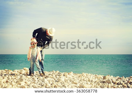 Happy father and his adorable little daughter playing on the beach - stock photo