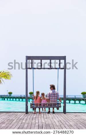 Happy father and his adorable little daughters at tropical beach having fun - stock photo