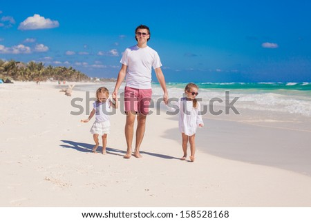 Happy father and his adorable little daughters walking on white sand beach in sunny day - stock photo