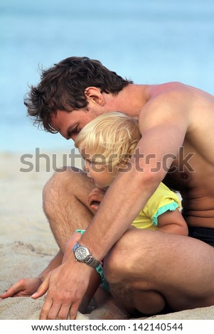 Happy father and his adorable little toddler daughter at beach
