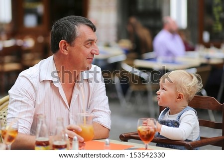 Happy father and his daughter, cute little baby girl, are having fun together in Italian cafe sitting at a table on outdoor terrace on a warm summer day, drinking refreshing ice tea and juice - stock photo