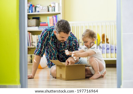 happy father and his little daughter opening box - stock photo