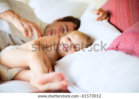 Happy father and his little daughter playing in bedroom