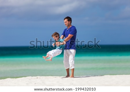 Happy father and his little son at tropical beach having fun during family summer vacation - stock photo