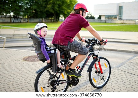 Happy father and his little toddler daughter riding a bike together in a city on summer day - stock photo