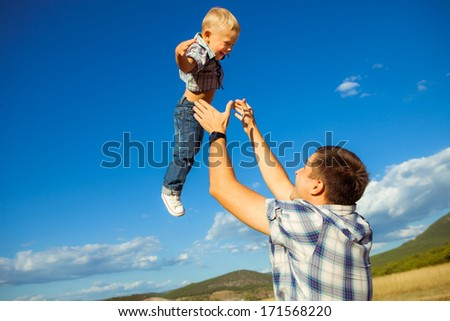 Happy father and his son playing together. Outdoors. Fun. Smiling. Lifestyle. Family Vacation.  - stock photo