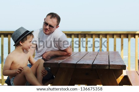 Happy father and his son sitting on summer cafe on the beach - stock photo