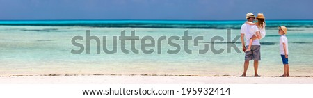 Happy father and kids at tropical beach during summer vacation - stock photo