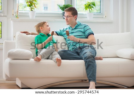 Happy father and little boy eating ice-cream on sofa - stock photo
