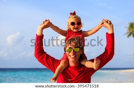 Happy father and little daughter at beach - stock photo