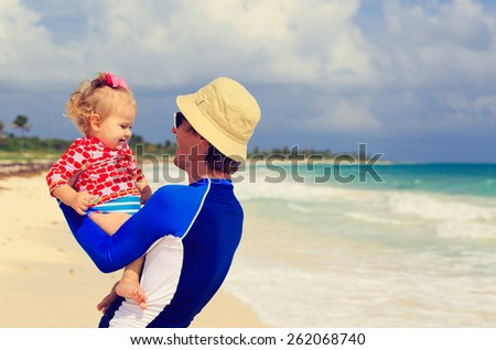 happy father and little daughter on summer beach - stock photo