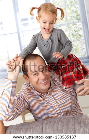 Happy father and little daughter playing at home, little girl climbing on father's shoulder, laughing.