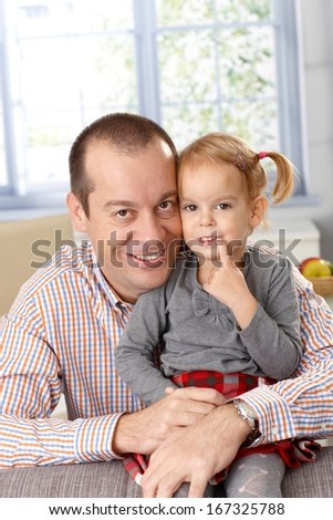 Happy father and little daughter smiling at home, looking at camera.