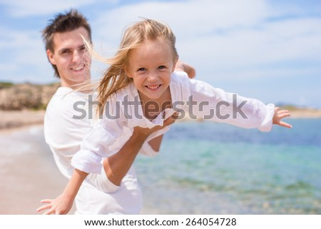 Happy father and little girl have fun during beach vacation - stock photo