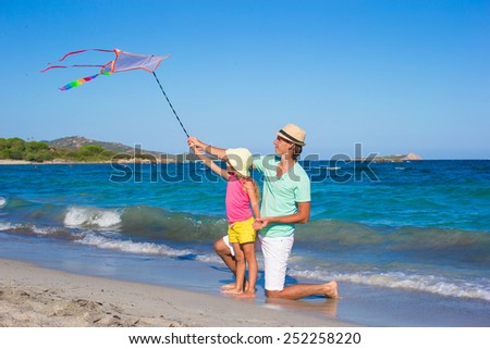 Happy father and little girl playing with kite during summer beach vacation