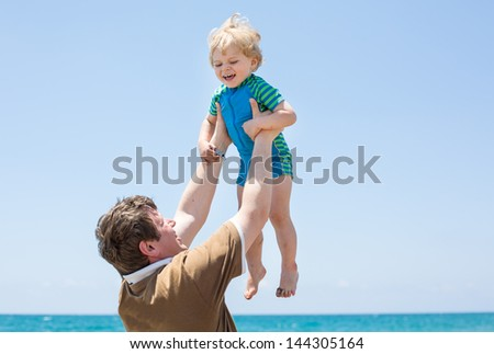Happy father and little son having fun at beach vacation - stock photo