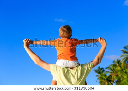 happy father and little son on shoulders play on sky at tropical beach