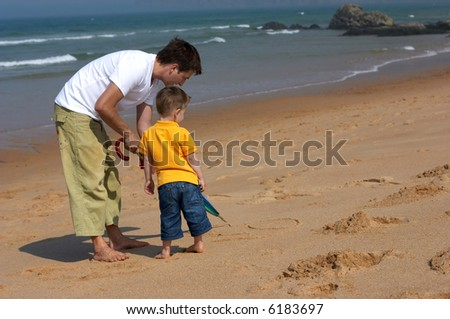 Happy father and son drawing picture on sandy beach