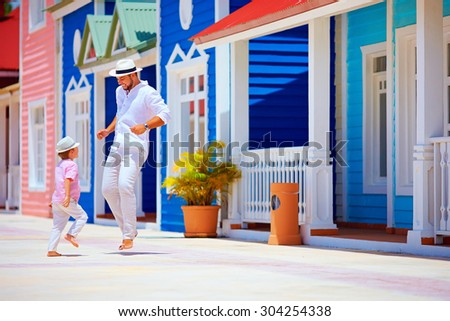 happy father and son enjoy life, dancing on caribbean village street - stock photo