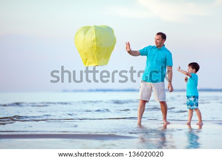 Happy father and son flying fire lantern together - stock photo