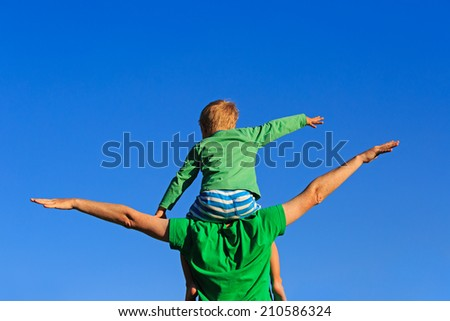 happy father and son flying on sky background - stock photo