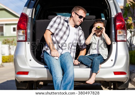 Happy father and son getting ready for road trip on a sunny day.  Concept of friendly family. - stock photo