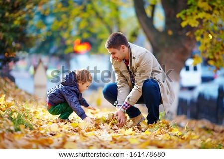 happy father and son having fun in autumn park - stock photo