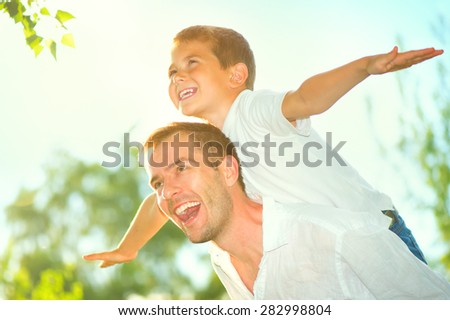 Happy Father and Son having fun outdoors. Laughing Dad with Little Boy enjoying nature together. Joyful Family. Free,freedom concept. Summer Holidays, vacation  - stock photo