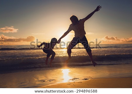 Happy father and son having fun together in sunset ocean on summer holidays - stock photo