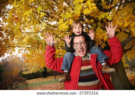 Happy father and son in autumn park - stock photo