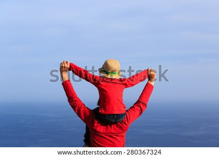 happy father and son on shoulders playing at the sea - stock photo