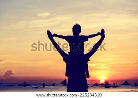 happy father and son on sunset beach vacation - stock photo