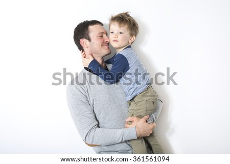 happy father and son play in front of a white wall - stock photo