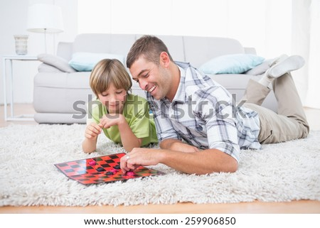 Happy father and son playing checker game while lying on fur at home - stock photo