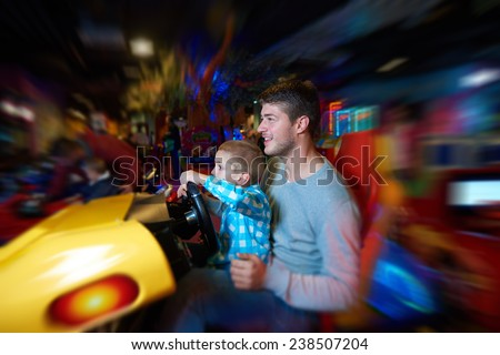 happy father and son playing driving wheel video game in playground theme park - stock photo