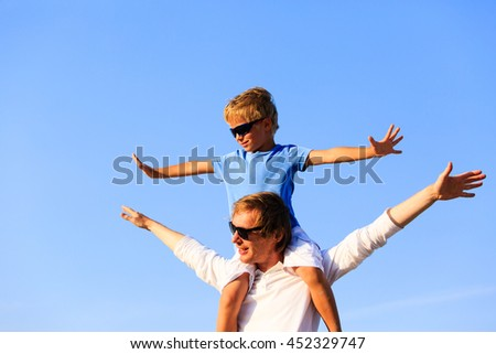 happy father and son playing on sky