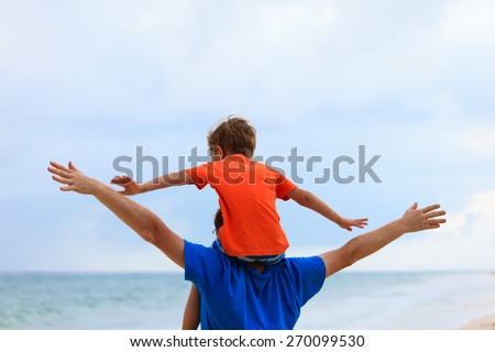 happy father and son playing on summer sea beach - stock photo