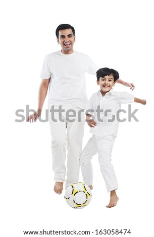 Happy father and son playing soccer - stock photo