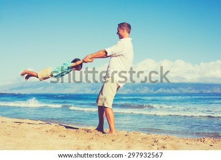 Happy father and son playing together at the beach. Fun vacation summer lifestyle.
