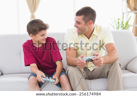 Happy father and son playing video game on sofa at home - stock photo