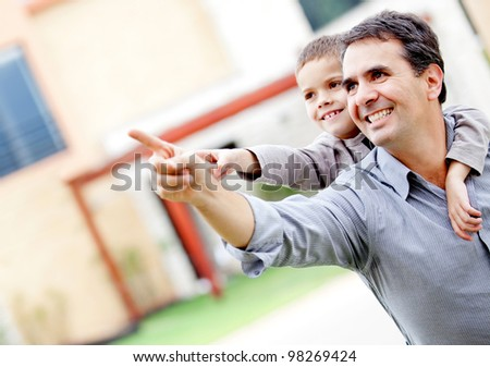 Happy father and son pointing away - outdoors - stock photo