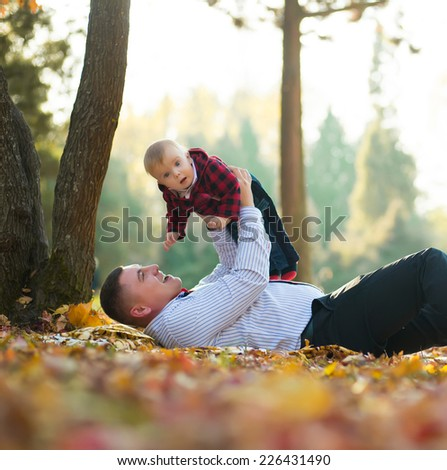Happy father and son portrait playing together having fun in yellow autumn park - stock photo