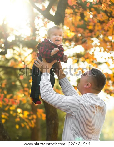Happy father and son portrait playing together having fun in yellow autumn park at sunrise - stock photo