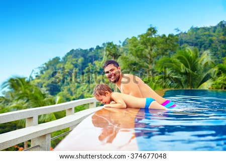 happy father and son relaxing in infinity pool on tropical island - stock photo