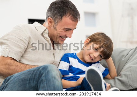 Happy Father And Son Sitting On Couch Enjoying - stock photo