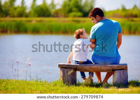 happy father and son sitting on the river bank - stock photo
