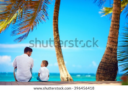 happy father and son sitting together near the seaside - stock photo